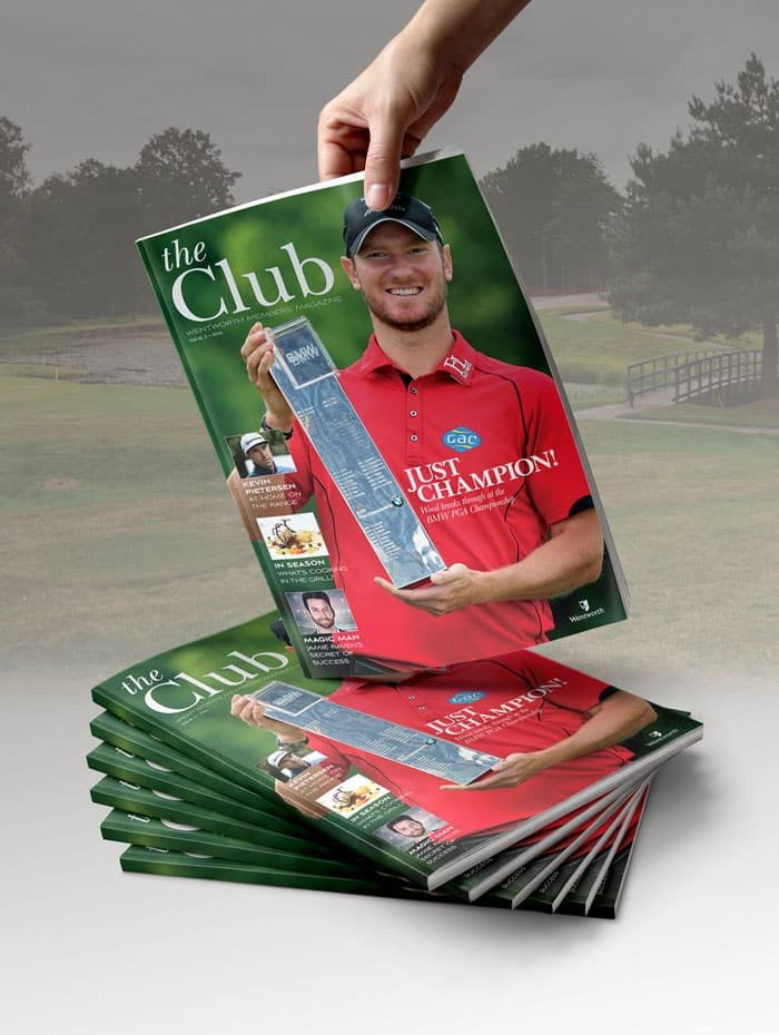 Hand holding up The Club magazine on top of pile